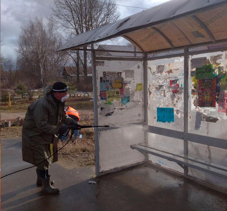 В городе Кимры люди в спецкостюмах обрабатывают остановочные павильоны